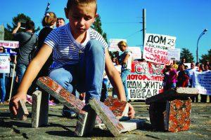 Мальчик строит дома из облицовочной гранитной плитки во время митинга обманутых дольщиков строительной компании СУ-155 на Суворовской площади города Москвы, Россия, 26 сентября 2015