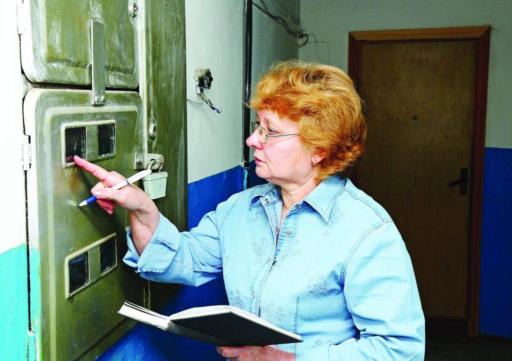 Женщина снимает показания квартирного электросчетчика