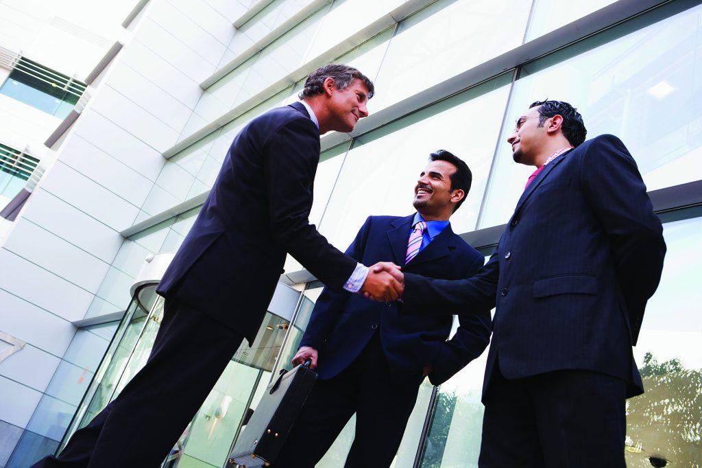 Деловые люди пожимают друг другу руки рядом со зданием офиса