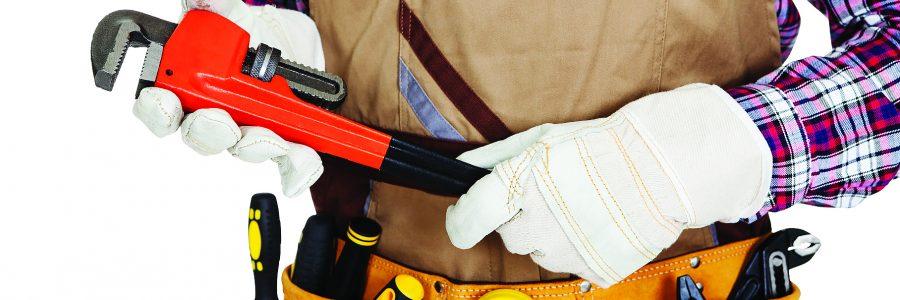 Строитель в поясе для инструментов и с разводным ключом в руках