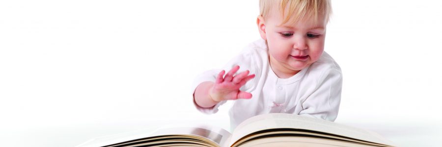 Baby Girl Is Pretending To Read A Large Book On White Background