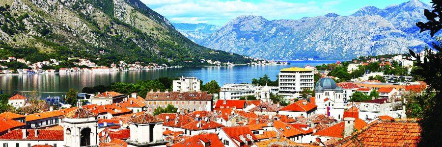 Montenegro. A view from above on the picturesque old town of Kotor with red tiled roofs and blue water of the Boka Kotor Bay on a sunny summer day (protected by UNESCO)