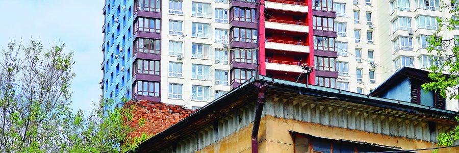 Город растет. Фрагмент старого ветхого жилого дома на фоне новостройки