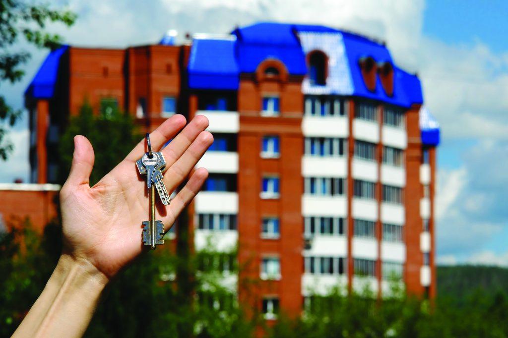 Мужская рука с ключами на фоне дома