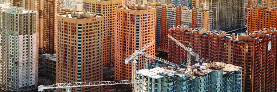 Вид сверху на строительную площадку жилого многоэтажного дома в новом микрорайоне