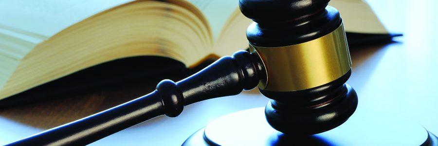 Судейский молоток с книгой на столе