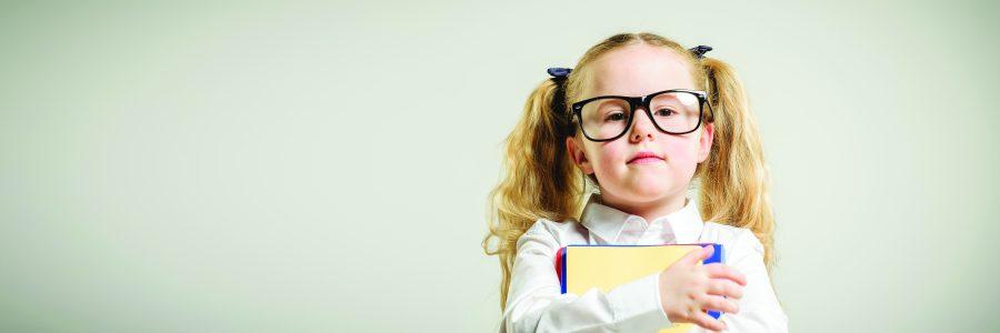 Schoolgirl in glasses reaching toward the school.